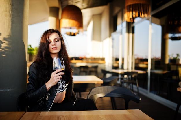 Jonge krullende vrouw die van haar wijn in een bar geniet.