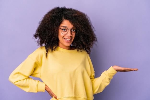 Jonge krullende vrouw geïsoleerde muur die een exemplaarruimte op een palm toont en een andere hand op taille houdt