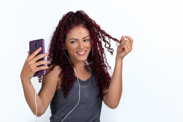 Jonge krullende vrouw in vrijetijdskleding die een selfie neemt