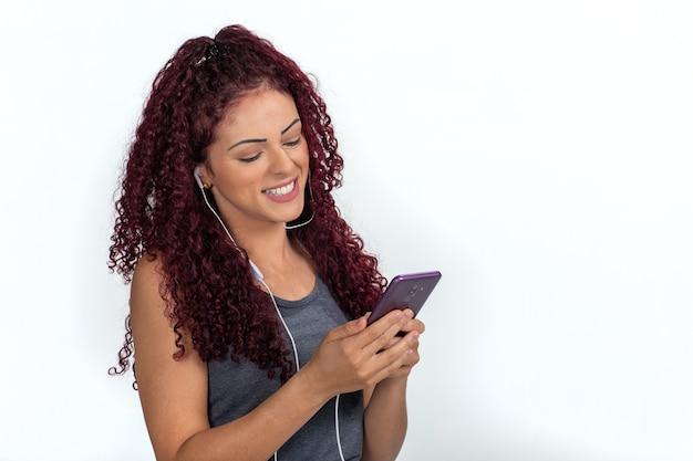 Jonge krullende vrouw in vrijetijdskleding met koptelefoon