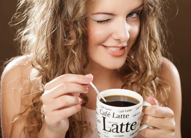 Jonge krullende vrouw koffie drinken