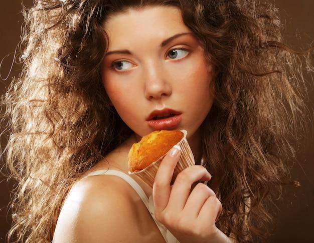 Jonge krullende vrouw met een cake, close-up