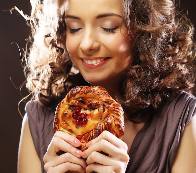 Jonge krullende vrouw met een cake