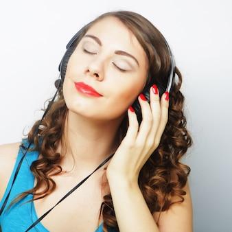 Jonge krullende vrouw met koptelefoon luisteren muziek.
