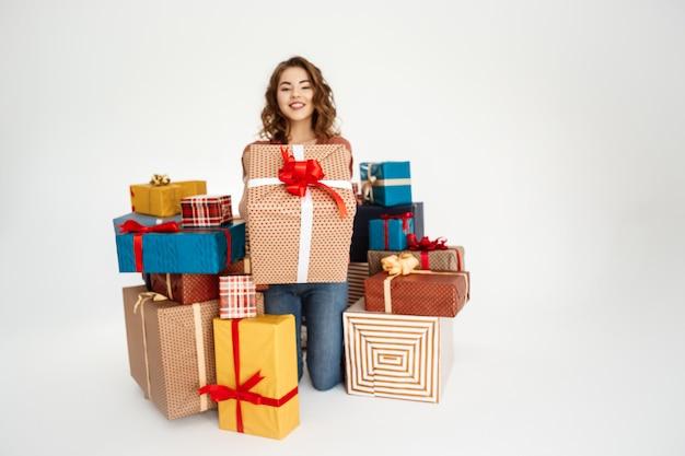 Jonge krullende vrouw onder geschenkdozen op wit