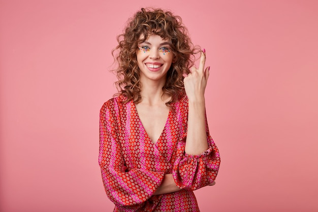 Jonge, krullende vrouwentribunes, glimlachend en haar op vinger draaiende, romantische gestreepte kleding dragen