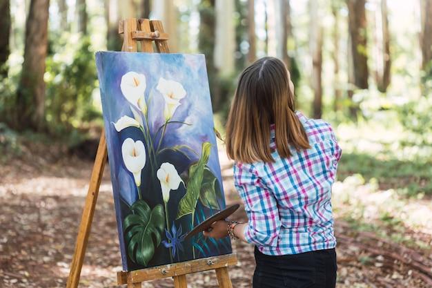 Jonge kunstenaar aan het werk aan zijn kunstwerken buitenshuis.