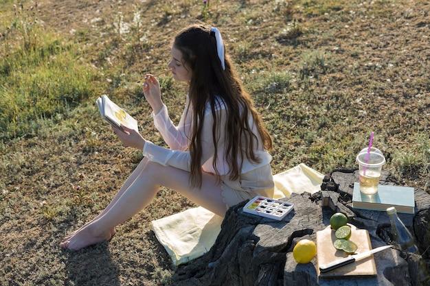 Jonge kunstenaar die een herfstlandschap schildert