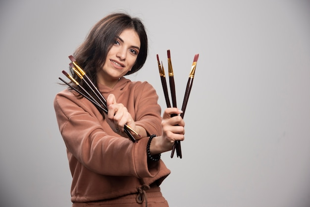 Jonge kunstenaar die haar zwarte verfborstels toont
