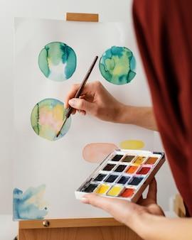 Jonge kunstenaar die met aquarellen schildert