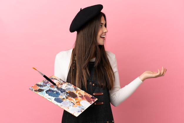 Jonge kunstenaar meisje met een palet geïsoleerd met verrassingsuitdrukking terwijl ze opzij kijkt