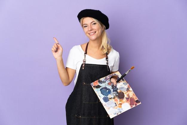 Jonge kunstenaar russische vrouw met een palet geïsoleerd op een paarse achtergrond die een vinger toont en optilt in teken van het beste