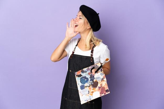 Jonge kunstenaar russische vrouw met een palet geïsoleerd op paarse achtergrond schreeuwen met mond wijd open aan de zijkant