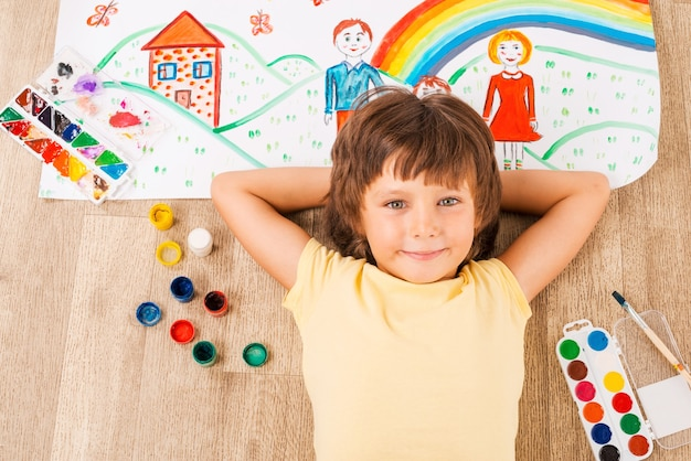 Jonge kunstenaar. schattige kleine jongen ontspannen tijdens het schilderen met aquarellen die op de vloer liggen