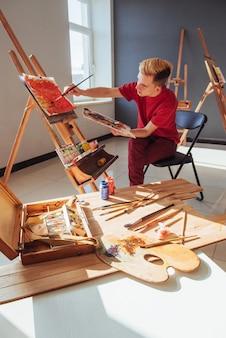 Jonge kunstenaar schildert een foto in de studio