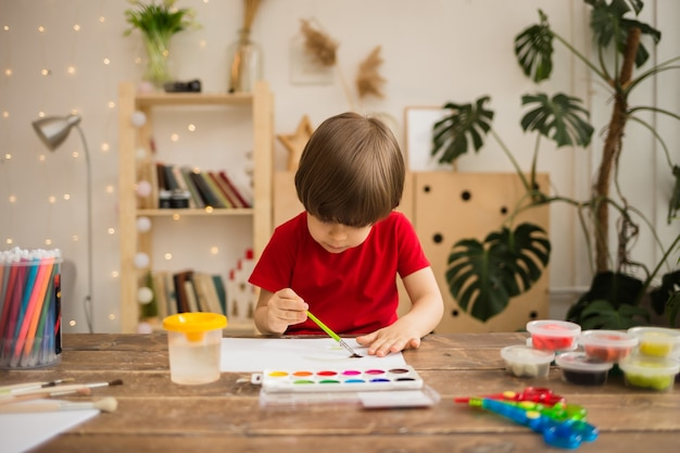 Jonge kunstenaar schildert op wit papier in een kamer
