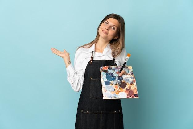 Jonge kunstenaar slowaakse vrouw die op blauwe muur wordt geïsoleerd die handen aan de kant uitbreidt om uit te nodigen om te komen