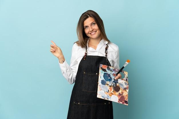 Jonge kunstenaar slowaakse vrouw geïsoleerd op blauwe achtergrond wijzende vinger naar de zijkant