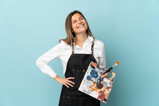 Jonge kunstenaar slowaakse vrouw geïsoleerd op blauwe muur poseren met armen op heup en glimlachen