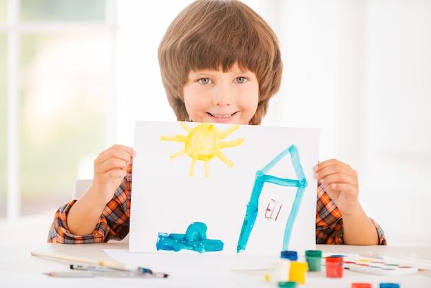 Jonge kunstenaar. vrolijke kleine jongen die ontspant tijdens het schilderen met aquarellen aan tafel