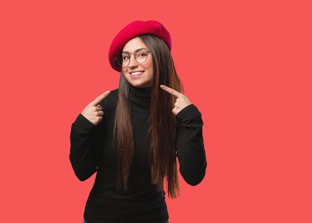 Jonge kunstenaar vrouw glimlacht, wijzend op mond