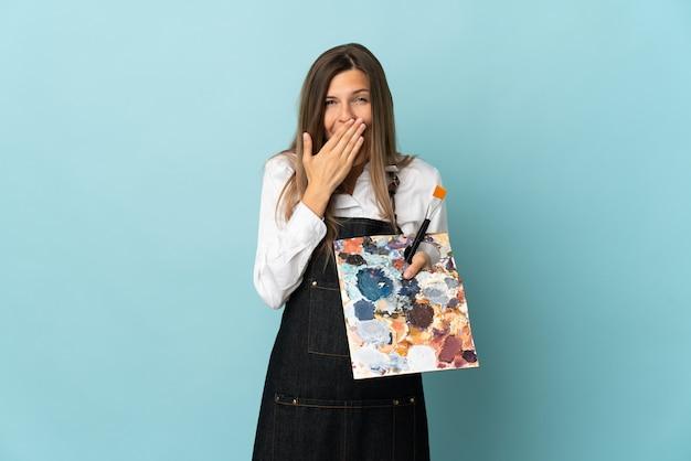 Jonge kunstenaars slowaakse vrouw die op blauwe muur gelukkig en het glimlachen behandelende mond met hand wordt geïsoleerd
