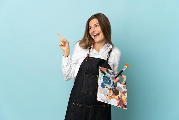Jonge kunstenaars slowaakse vrouw die op blauwe muur wordt geïsoleerd die vinger aan de kant richt en een product voorstelt