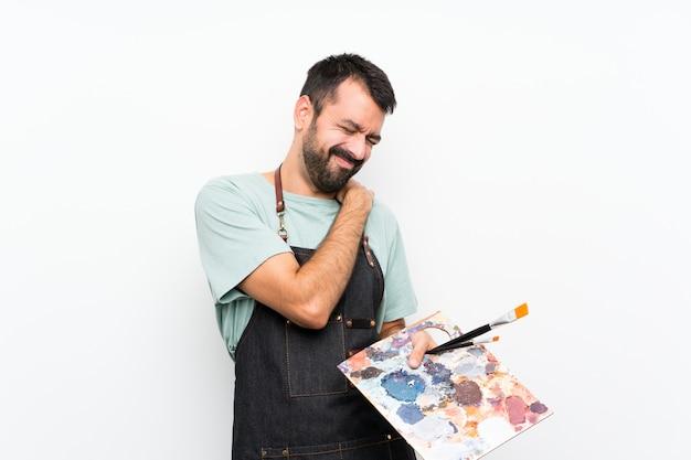 Jonge kunstenaarsmens die een palet houden die aan pijn in schouder lijden omdat hij zich heeft ingespannen