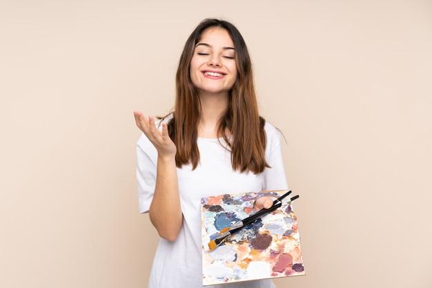 Jonge kunstenaarsmens die een palet op beige muur houden ongelukkig en gefrustreerd met iets
