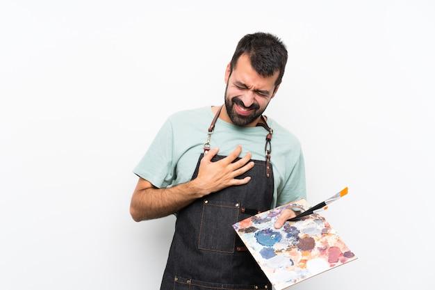 Jonge kunstenaarsmens die een palet over geïsoleerd houden hebbend een pijn in het hart