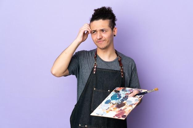 Jonge kunstenaarsmens die een palet over geïsoleerd paars houdt met twijfels en met verwarde gezichtsuitdrukking