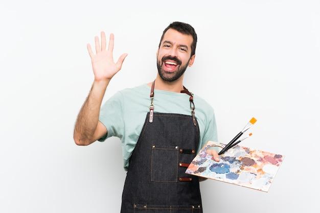 Jonge kunstenaarsmens die een palet over geïsoleerde muur groeten met hand met gelukkige uitdrukking