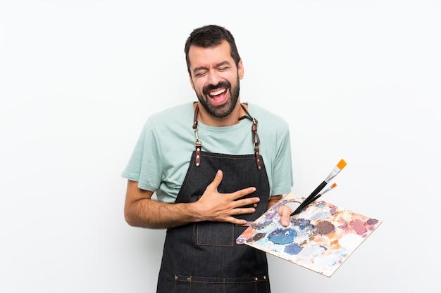 Jonge kunstenaarsmens die een palet over geïsoleerde muur houden die veel glimlacht