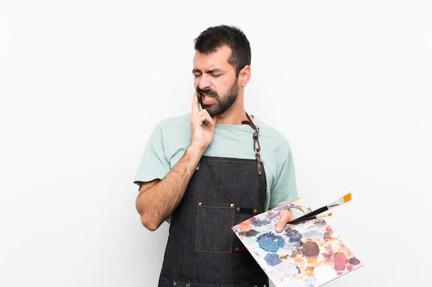 Jonge kunstenaarsmens die een palet over geïsoleerde muur met tandpijn houden