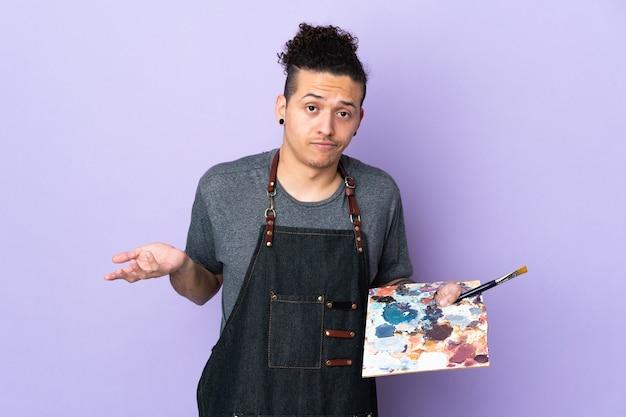 Jonge kunstenaarsmens die een palet over geïsoleerde purpere achtergrond houdt die twijfelsgebaar maakt terwijl hij de schouders opheft