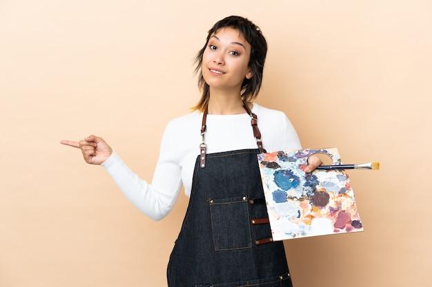 Jonge kunstenaarsmens die een palet over muur houdt wijzend aan de laterals die twijfels hebben