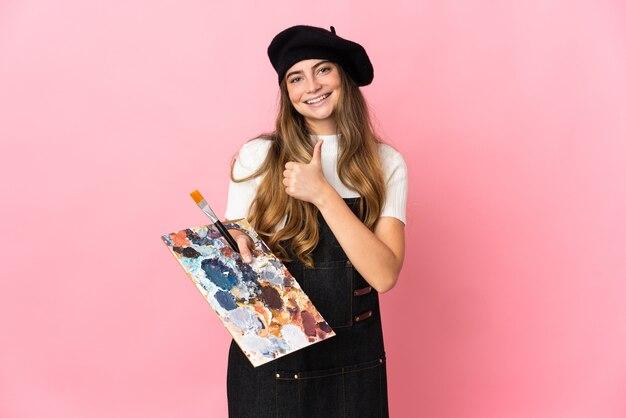 Jonge kunstenaarsvrouw die een palet houden dat op roze wordt geïsoleerdg die een duim omhoog gebaar geven