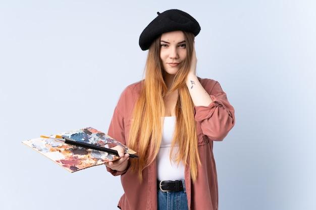 Jonge kunstenaarsvrouw die een palet houden die op blauwe muur wordt geïsoleerd ongelukkig en gefrustreerd met iets. negatieve gezichtsuitdrukking