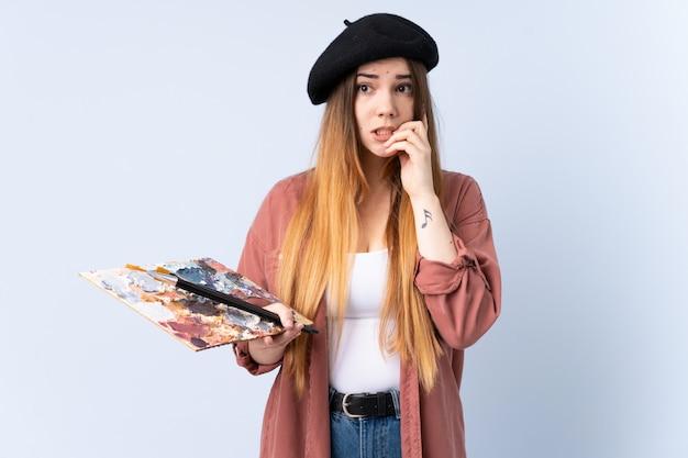 Jonge kunstenaarsvrouw die een palet houden die op blauwe zenuwachtig en doen schrikken muur wordt geïsoleerd