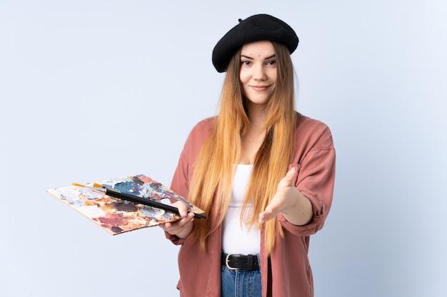 Jonge kunstenaarsvrouw die een palet op blauw muurhandenschudden houden na veel