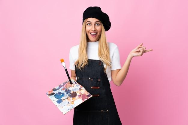 Jonge kunstenaarsvrouw die een palet op geïsoleerde roze wijzende vinger aan de kant houdt