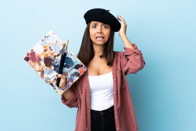 Jonge kunstenaarsvrouw die een palet over blauwe muur houdt die zenuwachtig gebaar doet.