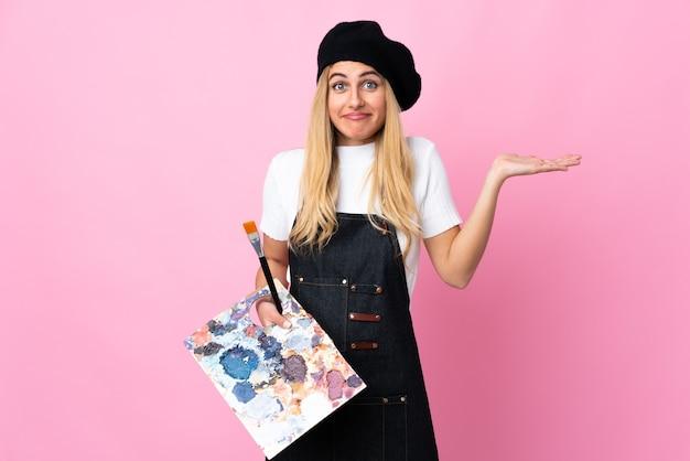 Jonge kunstenaarsvrouw die een palet over geïsoleerd roze houden die twijfels hebben met verwarde gezichtsuitdrukking