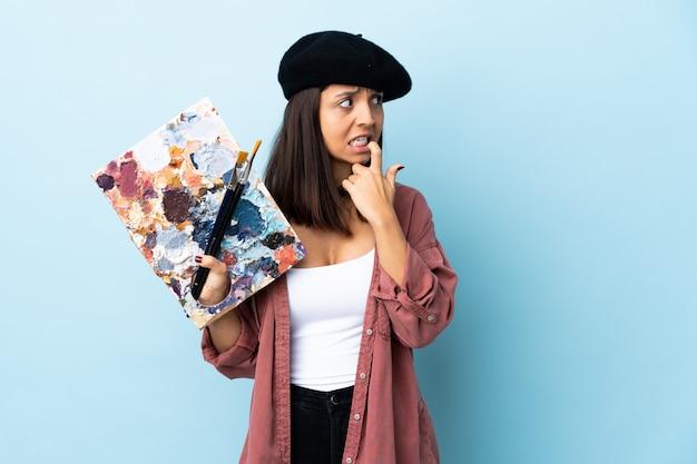Jonge kunstenaarsvrouw die een palet over geïsoleerd zenuwachtig en doen schrikken blauw houdt.