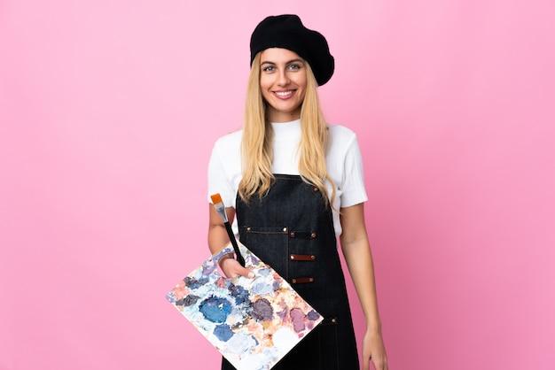 Jonge kunstenaarsvrouw die een palet over het roze muur toejuichen houdt