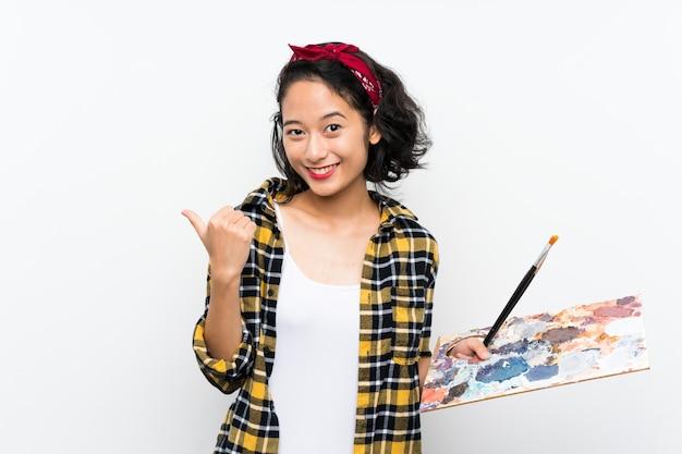 Jonge kunstenaarsvrouw die een palet over witte muur houden die aan de kant richten om een product te presenteren
