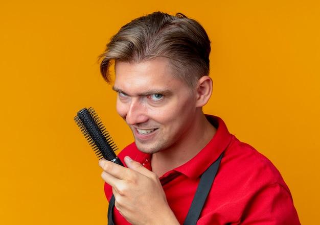 Jonge kwaad vrolijke blonde mannelijke kapper in uniform houdt haar kam geïsoleerd op oranje ruimte met kopie ruimte