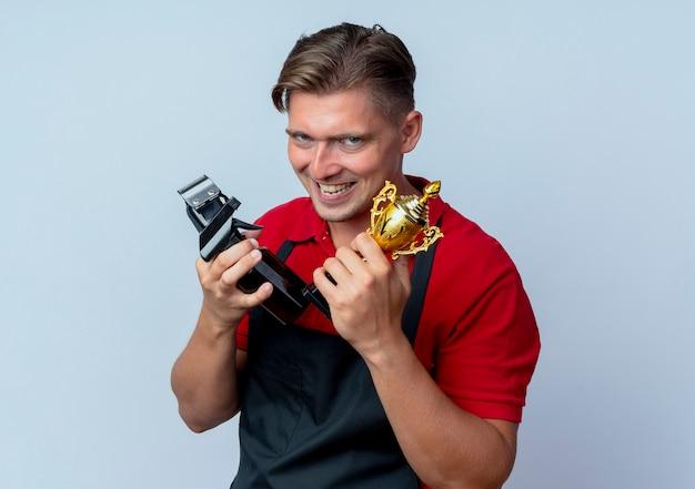 Jonge kwaad vrolijke blonde mannelijke kapper in uniform houdt kapper tools en winnaar beker geïsoleerd op witte ruimte met kopie ruimte