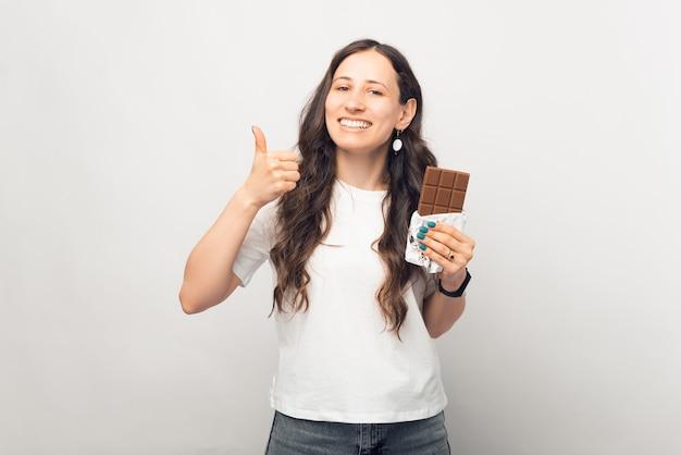 Jonge lachend naar de cameravrouw beveelt deze chocolade aan door duim omhoog te laten zien.