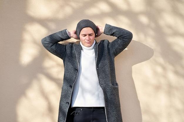 Jonge lachende aantrekkelijke hipster trendy man met gesloten ogen, gekleed in een grijze jas, witte trui en zwarte spijkerbroek poseren